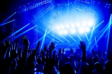 20924727 - rock concert, crowd of young people enjoying night performance, raised up and clapping hands, dance club, bright blue lights, music entertainment